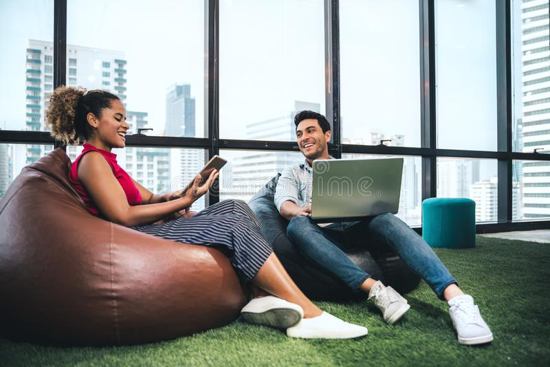 Couple of young designers working at modern office, two coworkers discussing fun project over a laptop, little team of royalty free stock photo