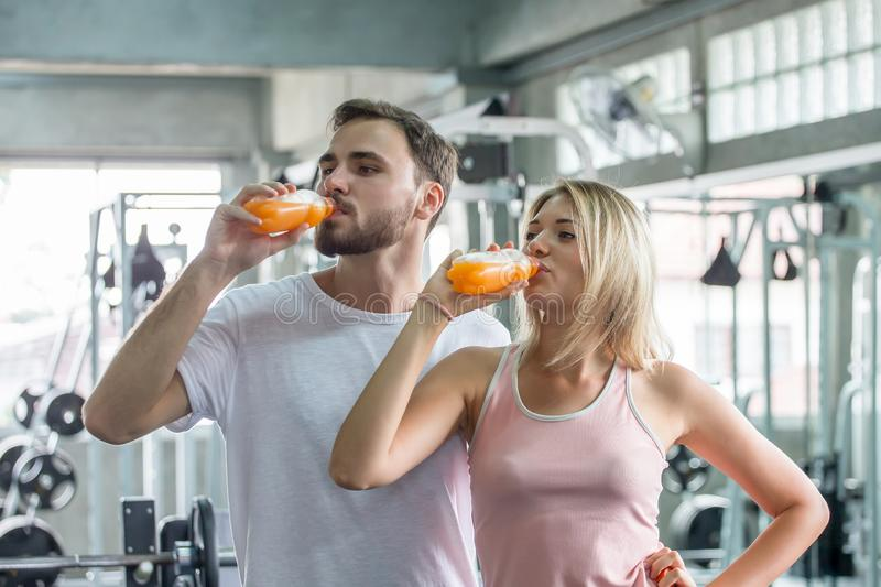 couple young fitness people drinking orange juice bottles in gym. sports man and woman exercises stock images