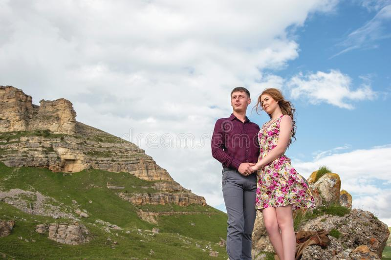 Couple Young guy with a girl holding hands standing and looking away in the background of a beautiful landscape of rocks stock photography