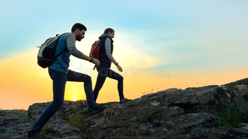 Young Happy Travelers Hiking with Backpacks on the Rocky Trail at Summer Sunset. Family Travel and Adventure Concept. stock image