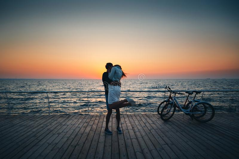 Couple of young hipster lovers kissing at the beach at sunrise sky at wooden deck summer time.  royalty free stock photos