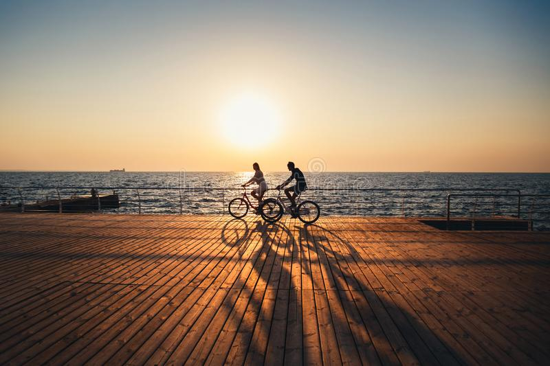 Couple of young hipsters cycling together at the beach at sunrise sky at wooden deck summer time royalty free stock photos