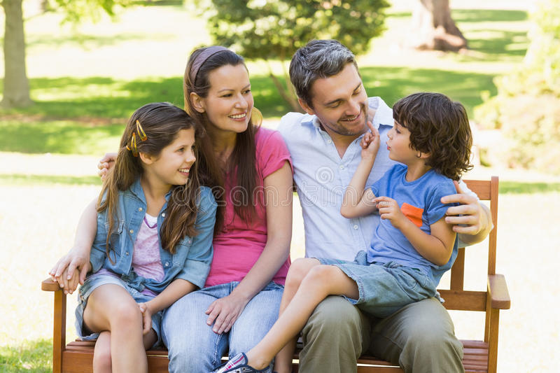 Couple with young kids sitting on park bench stock photos