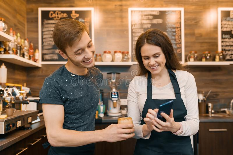 Couple of young male and female coffee shop owners near the counter, talking and smiling, coffee shop business concept royalty free stock photography