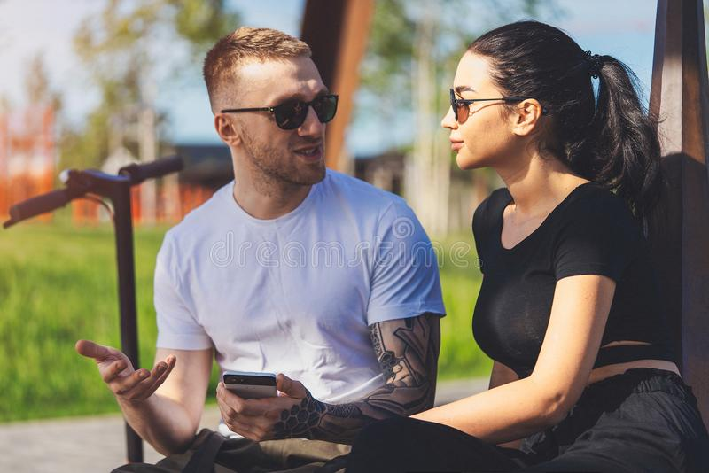 Couple of young man and woman sitting in park on wooden bench royalty free stock photo