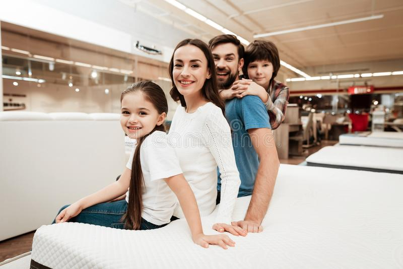 Couple of young parents with little daughter and son are sitting on orthopedic mattress in furniture store. stock image