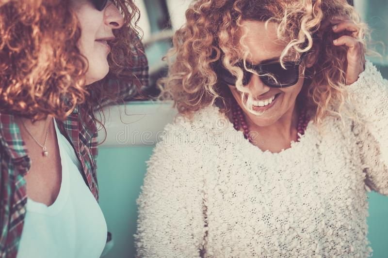 Couple of young pretty women together with curly blonde hair smile and enjoy the relationship or friendship - vintage color tones. Filter for middle age stock images