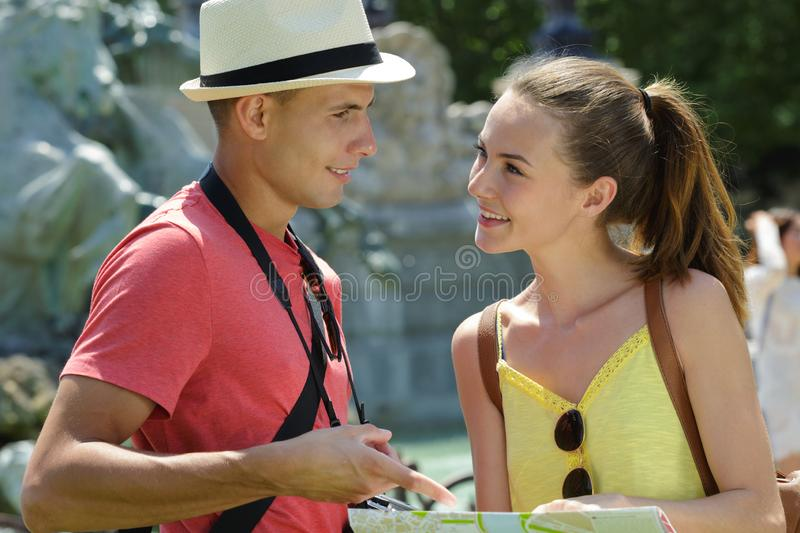 Couple young tourists reading map in city. Couple of young tourists reading a map in the city royalty free stock photos