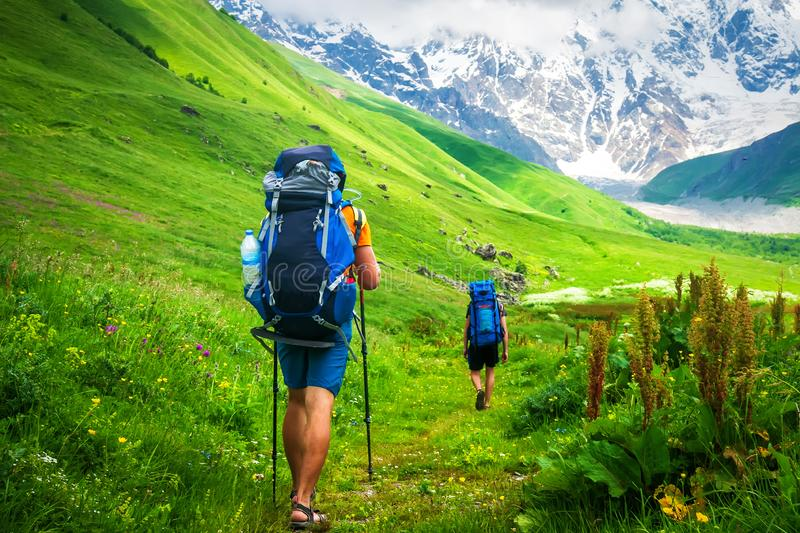 Couple of young travelers hiking with backpacks stock photos
