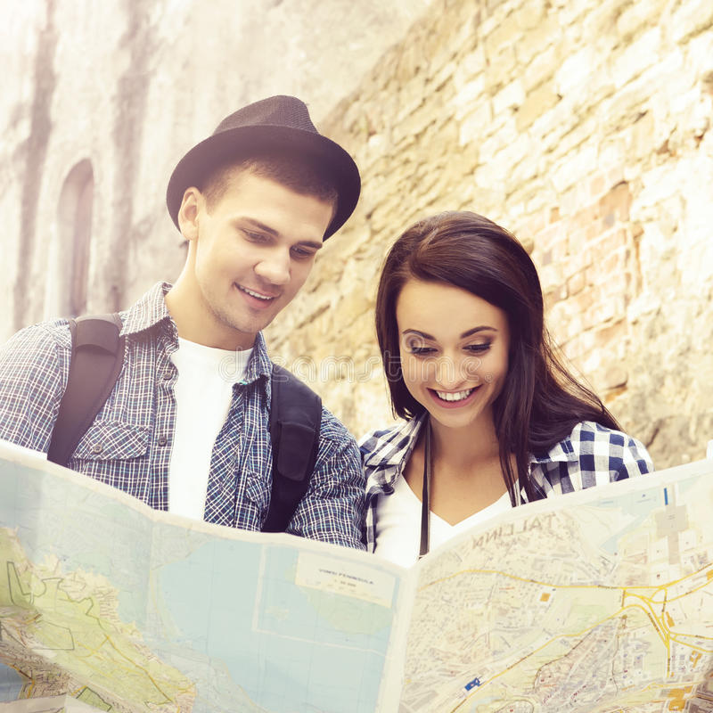Couple of young travelers with a map royalty free stock photography