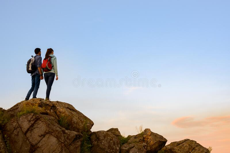 Couple of Young Travelers Standing on the Top of the Rock at Summer Sunset. Family Travel and Adventure Concept stock photos