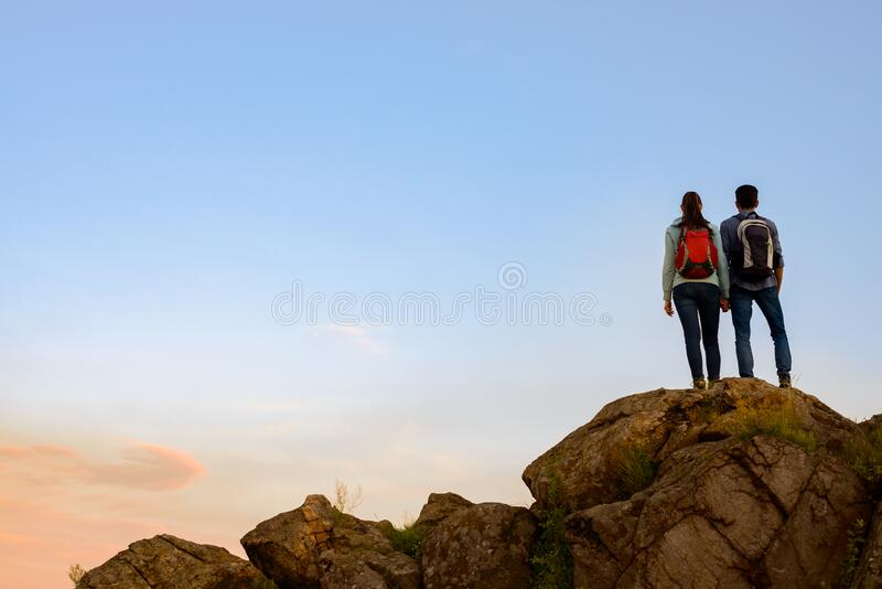 Couple of Young Travelers Standing on the Top of the Rock at Summer Sunset. Family Travel and Adventure Concept royalty free stock image