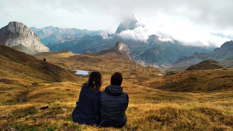 Couple of young travellers sitting on the grass looking to a valley with high mountains, lakes and clouds royalty free stock image