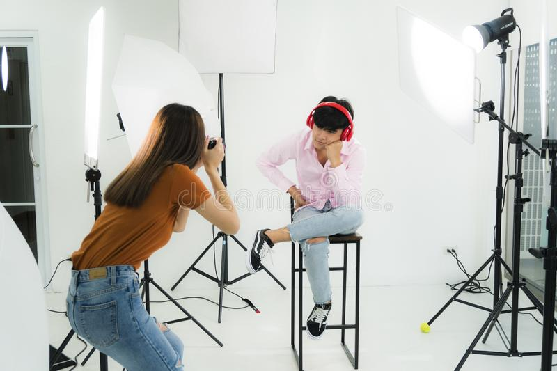 A couple of Young woman photographer and young man model. A couple of Young women photographer and young men model in pink shirt working in private photo studio stock photo