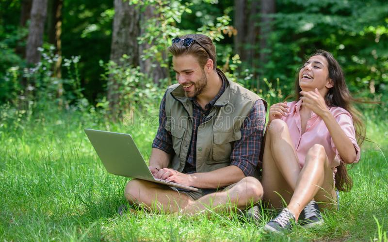 Couple youth spend leisure outdoors with laptop. Man and girl looking at laptop screen. Modern technologies give. Opportunity to be online and work in any stock photo