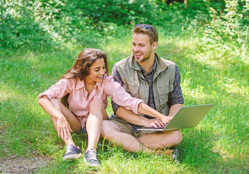 Couple youth spend leisure outdoors with laptop. Modern technologies give opportunity to be online and work in any. Environment conditions. Man and girl looking stock photo