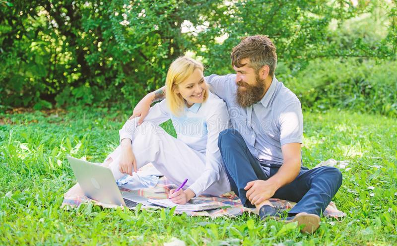 Couple youth spend leisure outdoors working with laptop. Couple in love or family work freelance. Modern online business. Freelance life benefit concept. How royalty free stock photo