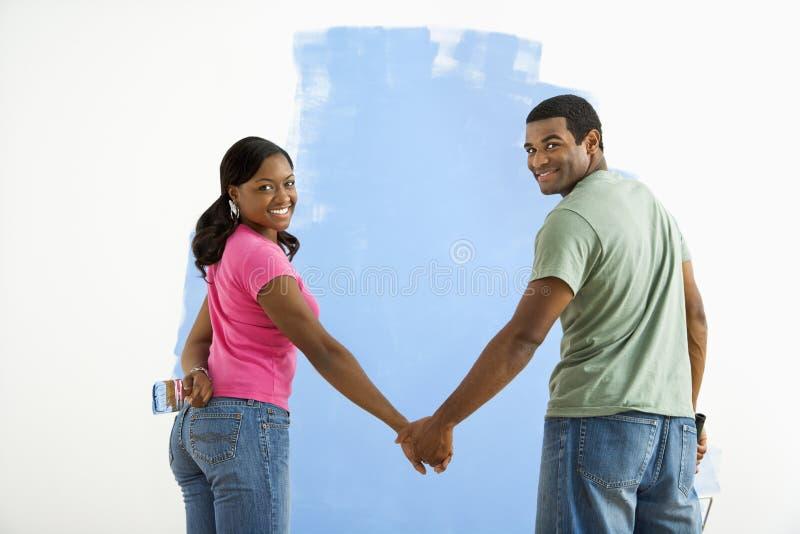Couples à côté de mur moitié-peint. photos stock