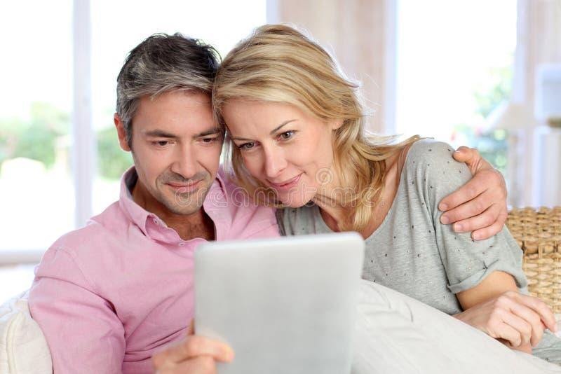 Couples à la maison travaillant au comprimé photo stock