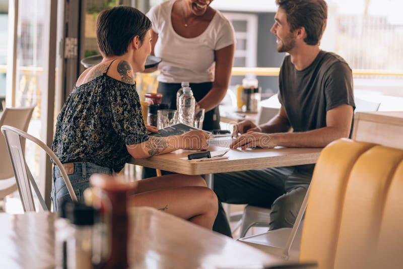 Couples à la nourriture de commande de restaurant photos stock