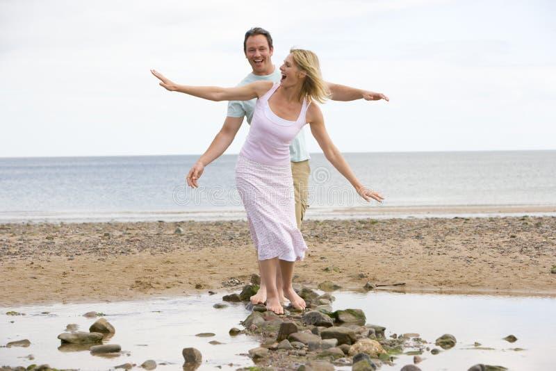Couples à la plage marchant sur des pierres et le sourire photos libres de droits