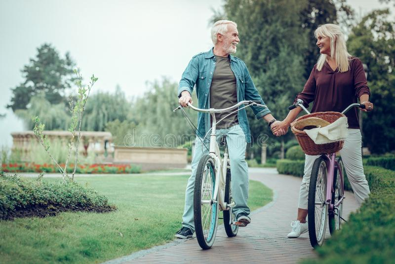 Couples âgés agréables tenant leurs mains ensemble image stock