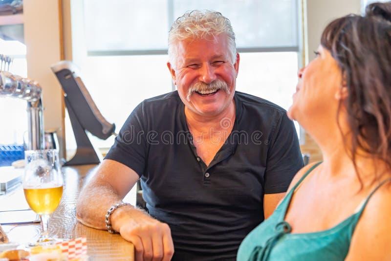 Couples âgés par milieu appréciant les bières froides à une barre de sports images libres de droits