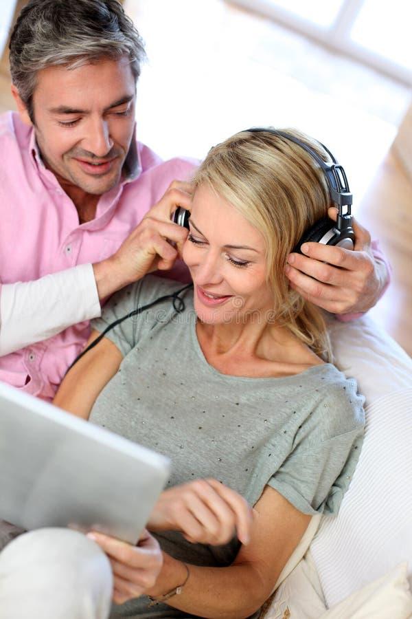 Couples écoutant la musique avec le comprimé photographie stock