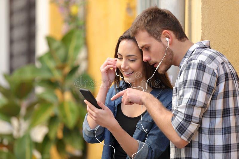 Couples écoutant la musique en ligne du téléphone intelligent photographie stock