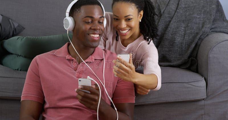 Couples écoutant la musique et prenant la photo avec les téléphones intelligents photos stock