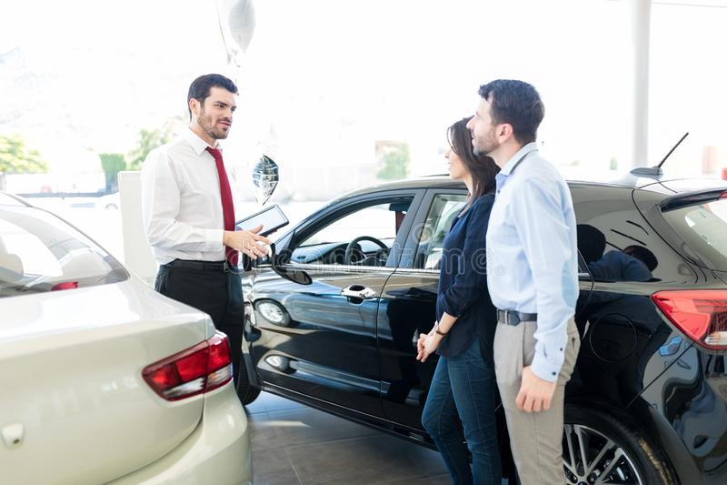 Couples écoutant le vendeur de voiture With Trust photo stock