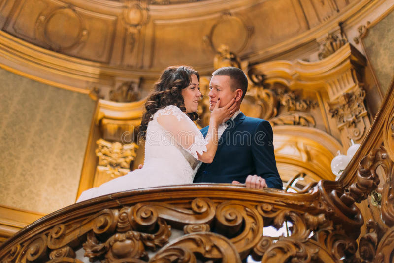Couples élégants élégants de nouveaux mariés embrassant affectueusement dans l'intérieur luxueux du vieux manoir classique image libre de droits