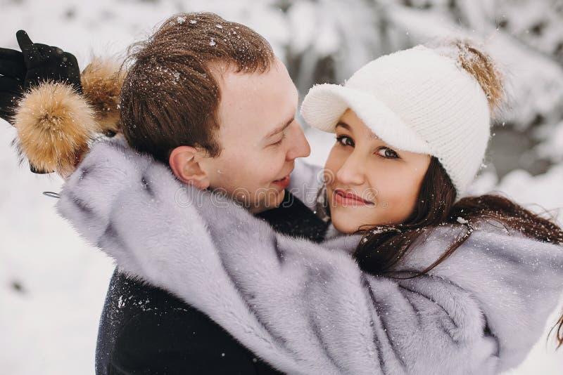 Couples élégants dans l'amour étreignant en montagnes neigeuses d'hiver Portra photos stock