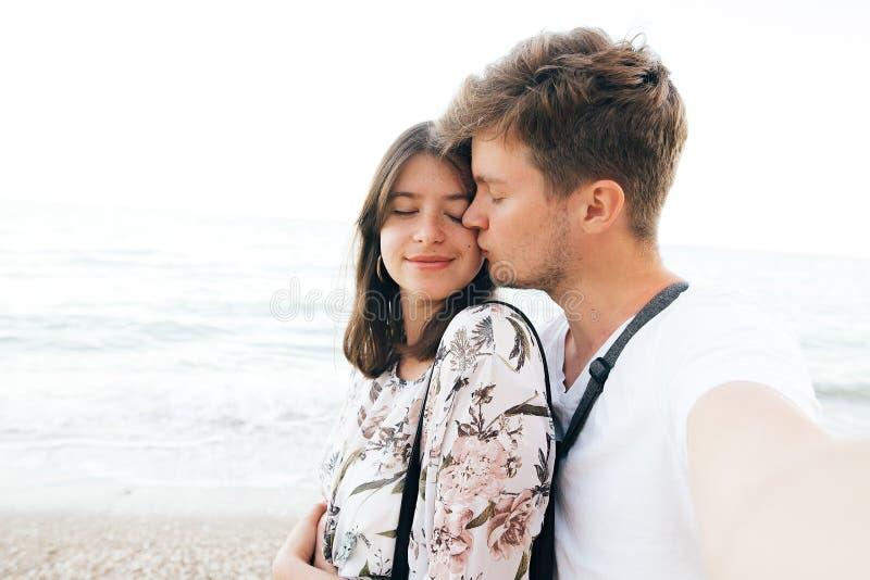 Couples élégants de hippie prenant le selfie sur la plage et l'embrassant à égaliser la mer Vacances d'?t? Portrait de jeune fami photos stock