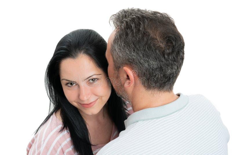 Couples étreignant avec la femme regardant la caméra photographie stock libre de droits