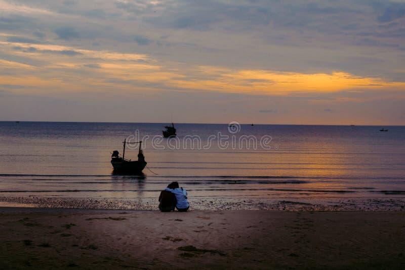 Couples étreignant sur la plage sur le lever de soleil photos libres de droits