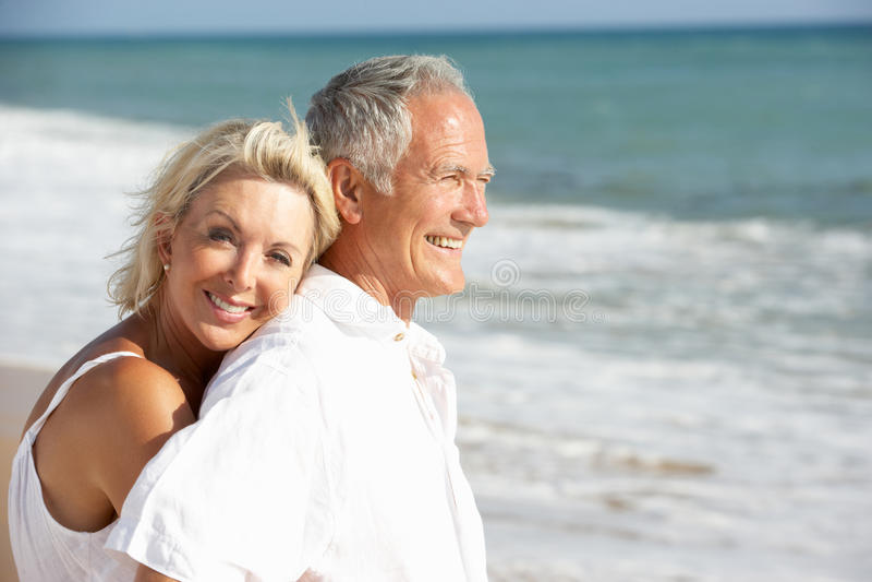 Couples aînés appréciant des vacances de plage au soleil photos stock