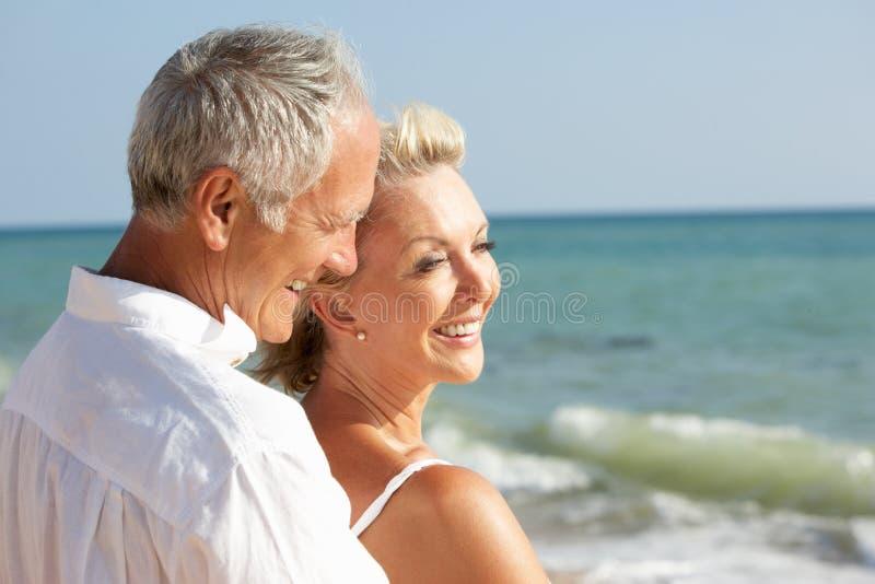 Couples aînés appréciant des vacances de plage au soleil images stock