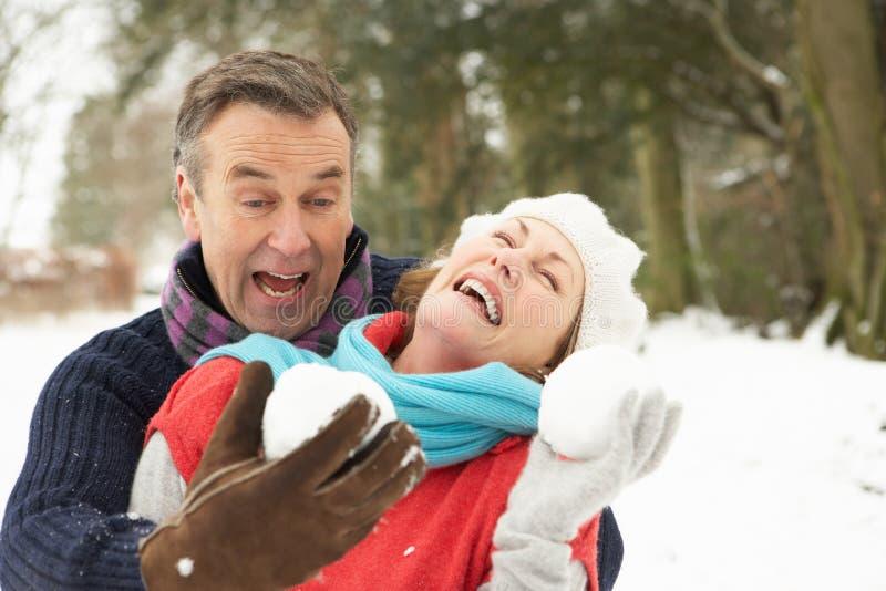 Couples aînés ayant le combat de boule de neige photos stock