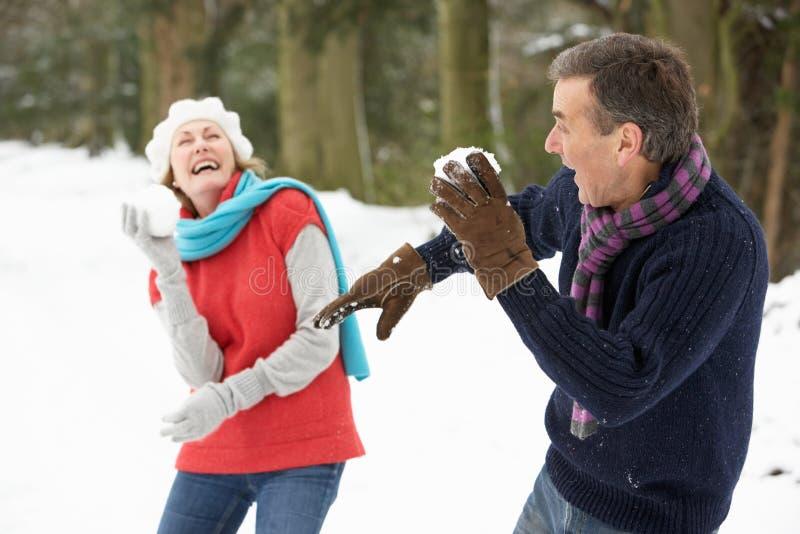 Couples aînés ayant le combat de boule de neige dans la neige images libres de droits