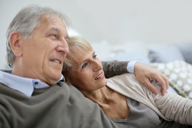 Couples aînés détendant sur le sofa photos stock