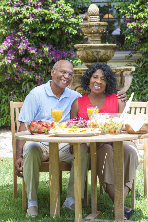 Couples aînés d'Afro-américain mangeant à l'extérieur images libres de droits