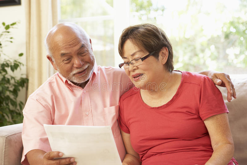 Couples aînés discutant le document à la maison photographie stock libre de droits