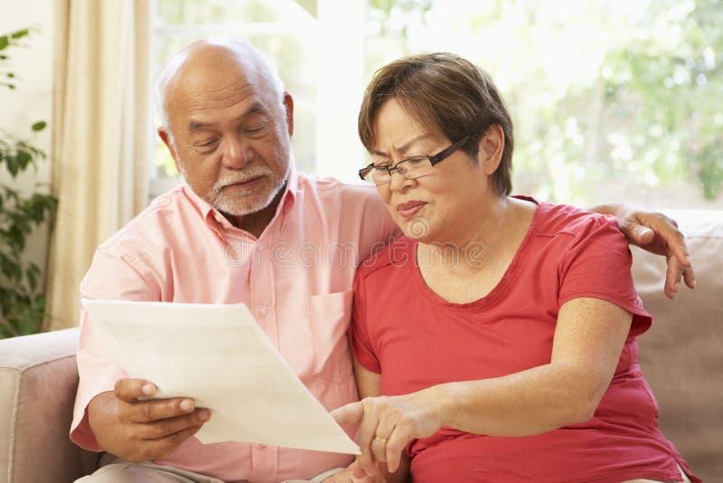 Couples aînés discutant le document à la maison photos libres de droits