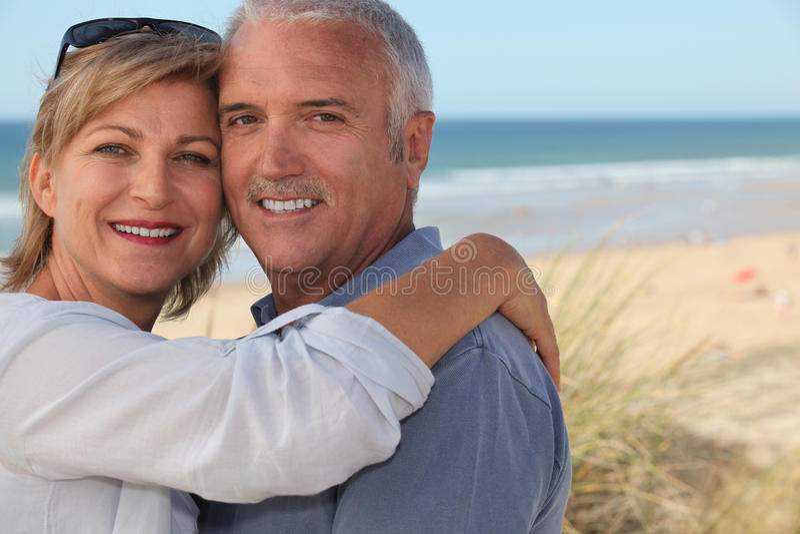 Couples aînés embrassant sur la plage photos libres de droits
