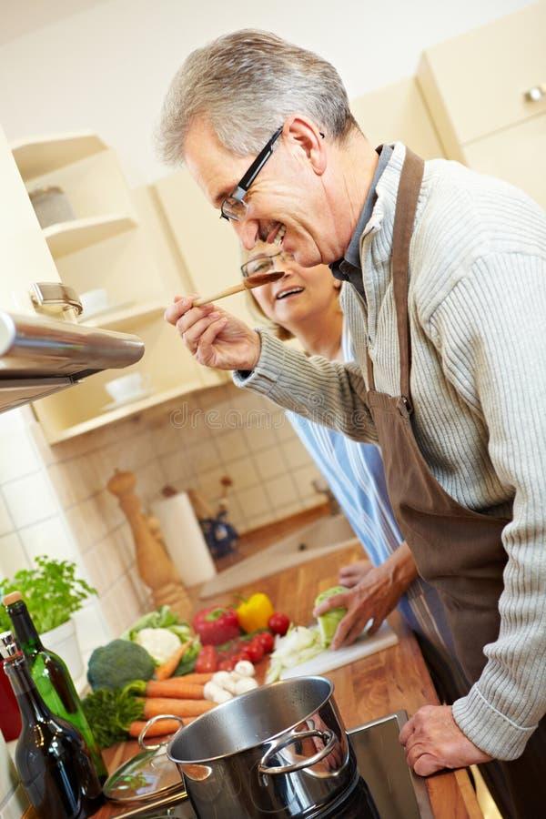 Couples aînés faisant cuire le potage photos stock