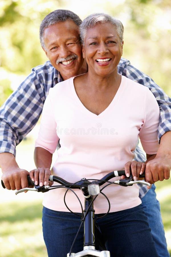 Couples aînés faisant un cycle en stationnement photo stock