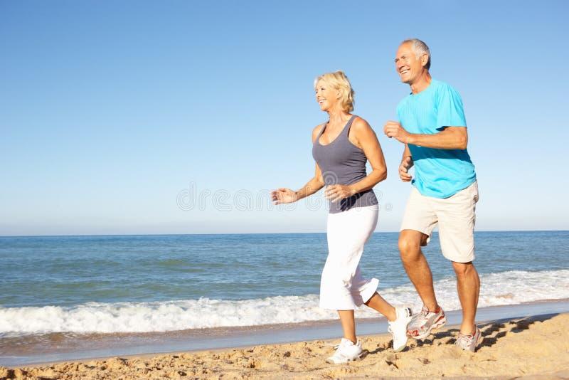 Couples aînés fonctionnant le long de la plage image stock