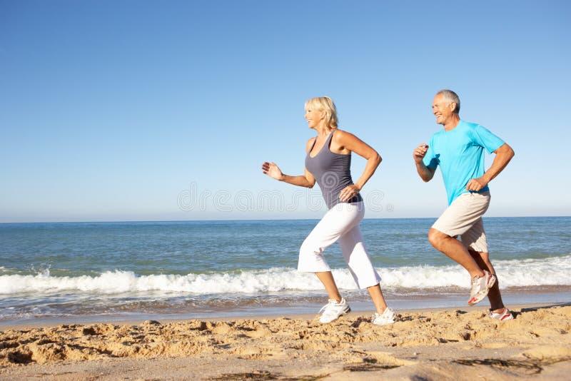 Couples aînés fonctionnant le long de la plage image libre de droits