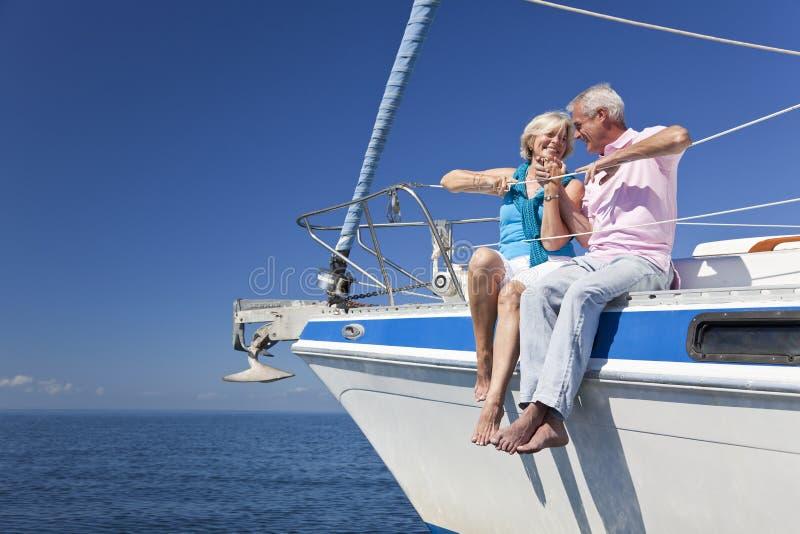 Couples aînés heureux se reposant sur un bateau à voile image libre de droits
